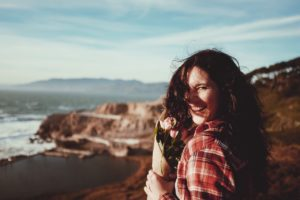 woman smiling on beach benefits of invisalign