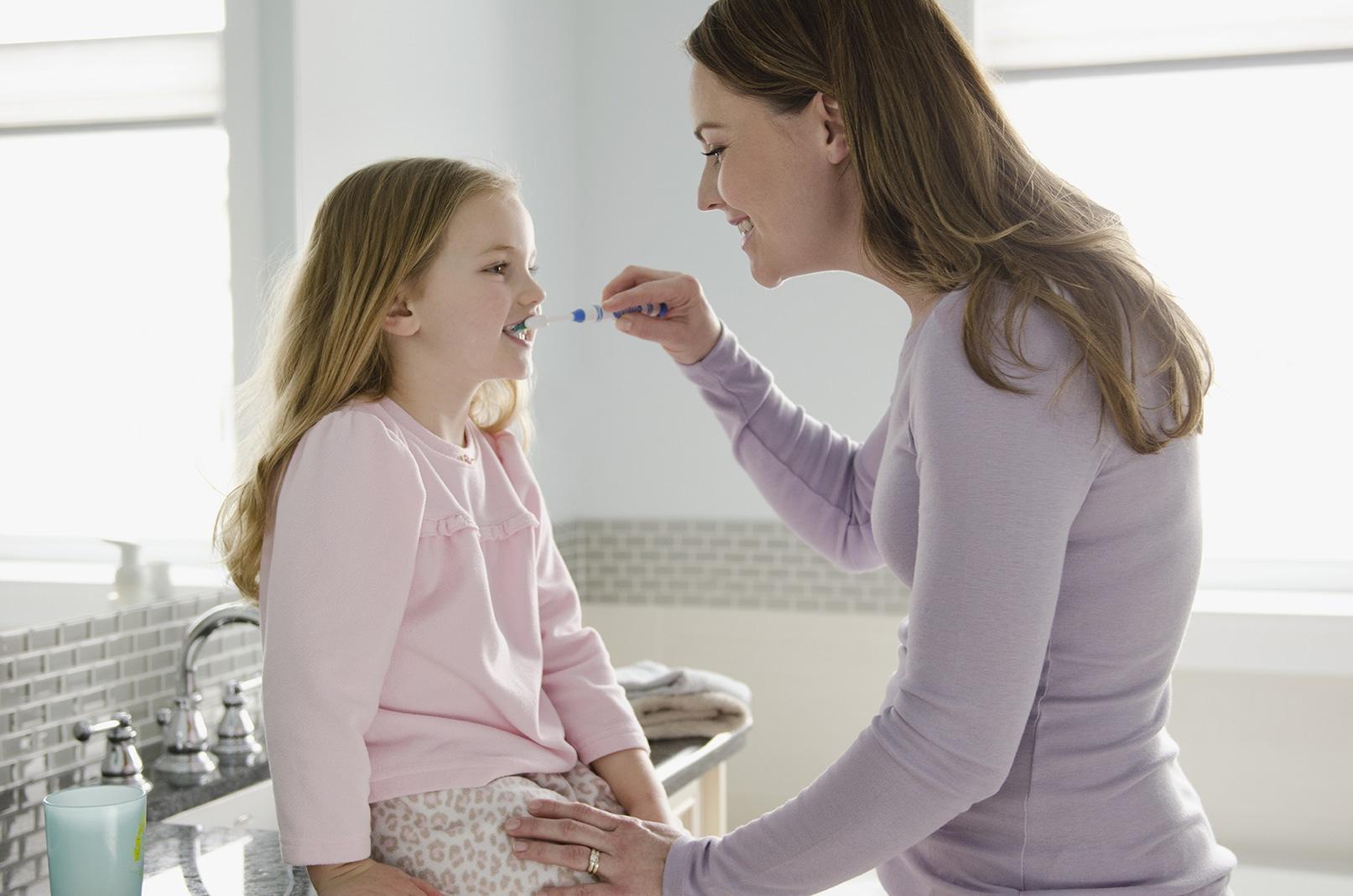 Mom brushing child's teeth