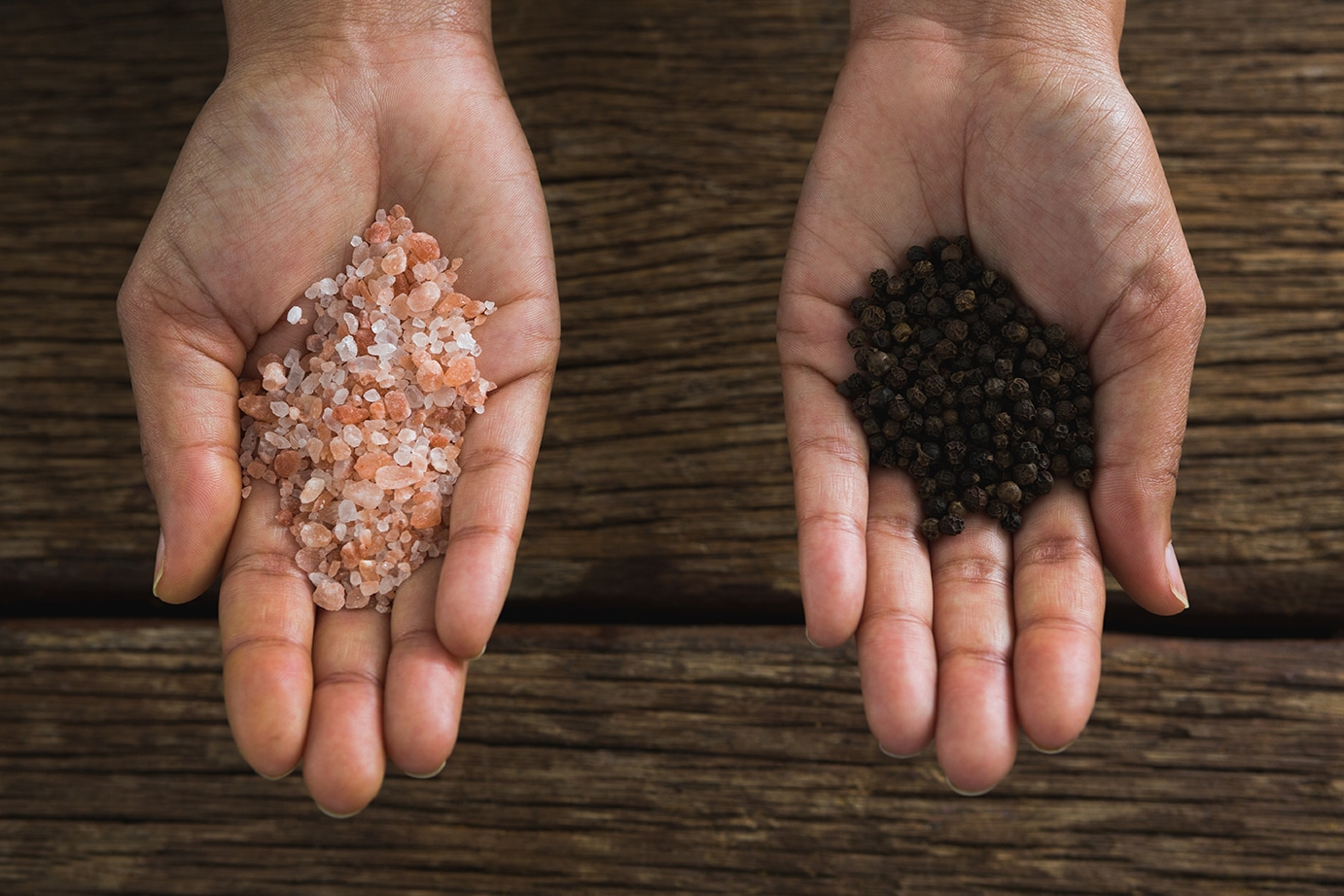 how to prevent tooth decay naturally -Hands holding sea salt and black pepper seeds
